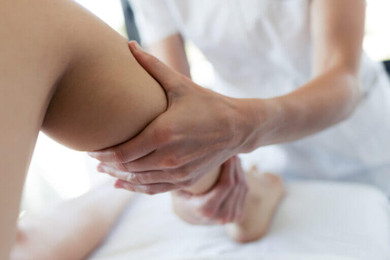 Close-up of masseur massaging the pregnant woman's legs in spa center.