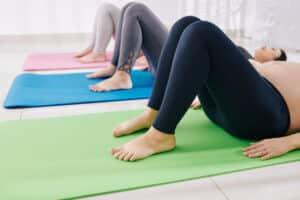 groupe de femme enceinte faisant de l'exercice dans une salle sur des tapis de yoga