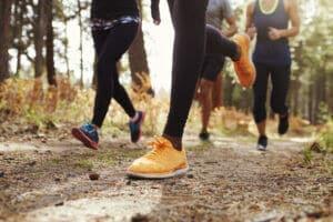jambes et chaussures de jeunes adultes courrant en foret