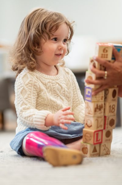 A preschool age girl with a prosthetic leg is at a medical appointment. The child is meeting with her physical therapist. The child is sitting on the floor building with wooden toy blocks. The medical professional is sitting on the floor assisting the girl. The child is smiling up at the doctor.