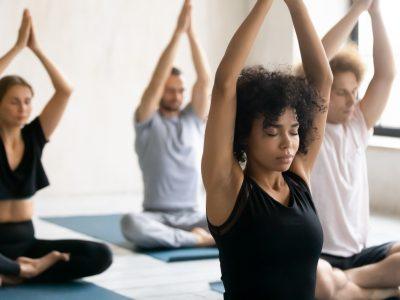 During morning routine yoga session after work out diverse people relaxing seated cross-legged practising meditation closed eyes raised arms up performing Namaste gesture, focus on mixed-race trainer